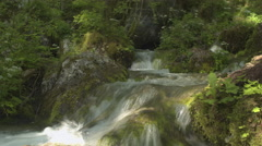 CLOSE UP: Whitewater river cascades and waterfalls falling over mossy rocks - stock footage