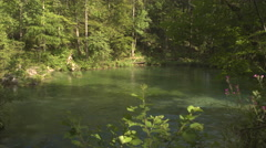 River running into beautiful crystal clear mountain lake in sunny spring forest - stock footage