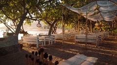Beachside restaurant with wooden furniture in Pemuteran Bay, Bali on sunrise Stock Footage