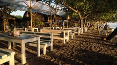 Beachside restaurant with wooden benches and tables on sunrise Stock Footage