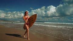Young slim woman walks on Bali Seminyak beach with a surfboard Stock Footage