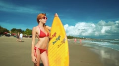 Young slim woman stands on Bali Seminyak beach with a surfboard Stock Footage