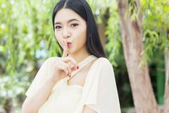 Beautiful Asian woman with her top secret gesture Stock Photos
