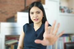 Asian woman with her hand signaling stop (only face is in focus) - stock photo