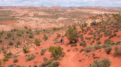 People hiking through hot desert in Utah Stock Footage