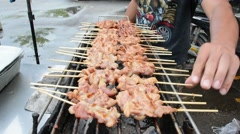 Sticks of grilled skewer pork food being cooked on charcoal grill in Thailand Stock Footage