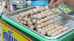 Sticks of skewer grilled meatballs on the tray for sale in Thailand market Stock Footage