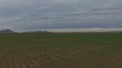 4K Aerial drone rainy cloudy sunrise over a desert farm forward Stock Footage
