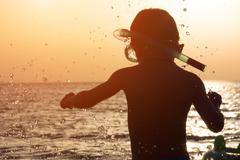 little boy with mask and snorkel on background of sea sunset - stock photo