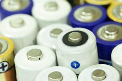 Pile of colorful batteries stacked in a row together Stock Photos