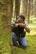 Interracial hunter in the forest - stock photo