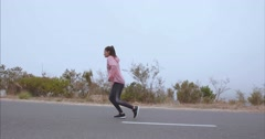 Fitness woman running on countryside road - stock footage