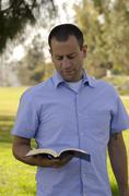 Man reading bible in the park. Stock Photos