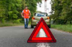 Broken car on the road and red warning triangle - stock photo