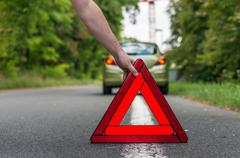 Driver putting out a traffic warning sign - broken car on the road - stock photo