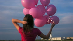 Slender girl unties the balloons and takes them herself Stock Footage