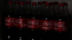 Coca-Cola in refrigerator. In shop lights being turned on in preparation for Stock Footage
