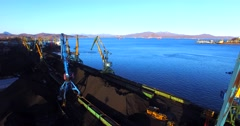 Aerial panoramic view of the cargo cranes, loading coal into the bulk cargo ship - stock footage