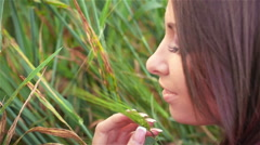 Young slender girl holding a green ear of wheat - stock footage