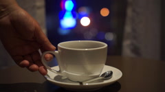 Drinking coffee beside window, with backgrounds of colorful city lights Stock Footage