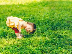 One-year baby girl playing upside down on the street Stock Photos