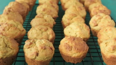 Slow motion of baker hand taks one mini Muffins cake out off cooling rack Stock Footage
