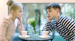 Girl and boy are drinking tea in a cafe on the background of the summer window Stock Footage