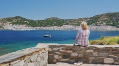 Steadicam shot: Woman tourist in sunglasses admire the sea views. Against the - stock footage