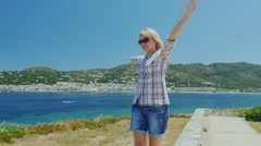 Steadicam shot: Young woman enjoys relaxing in the Mediterranean resort. Waving Stock Footage
