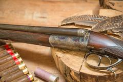 Vintage hunting gun, feathers, hunting belt with cartridges, hunting horn - stock photo
