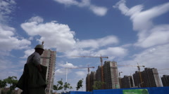 Workers walking to a huge residential construction site Stock Footage