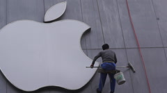Worker cleaning an Apple shop's icon Stock Footage