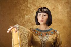 Beautiful Egyptian woman like Cleopatra pointing finger away on golden Stock Photos