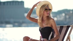 Sexy blond woman sitting on sun lounger on beach - stock footage