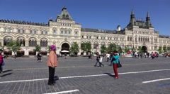 Aged asian couple make pictures on Red Square, woman hold camera Stock Footage