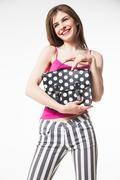 Smiling brunette hugging polka dot fashion bag - stock photo