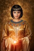 Beautiful Egyptian woman like Cleopatra with magic ball on golden background Stock Photos