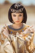 Beautiful woman with fashion make-up and hairstyle like Egyptian queen Cleopatra Stock Photos