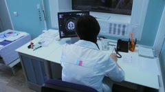 Woman doctor in a hospital looks tomography brain on the monitor Stock Footage
