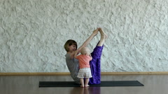 The young blonde girl practicing yoga with her child in the hall. HD Stock Footage