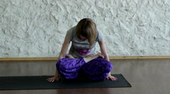 The young blonde girl practicing yoga in the hall. The lotus position. HD Stock Footage