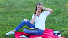 Young Female using tablet eating french fries junk food - stock footage