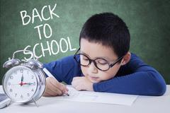 Boy with alarm clock drawing in class Stock Photos