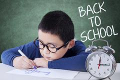 Schoolboy back to school and drawing on desk - stock photo