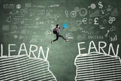 Student jumping with text of Learn and Earn - stock photo