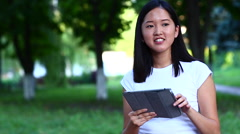 Young beautiful Asian uses a tablet waves and look to camera in the green park Stock Footage