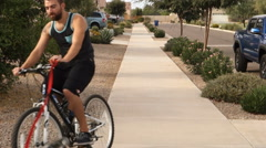 Dog Pulls Bicycle Rider on Typical Arizona Neighborhood Sidewalk Stock Footage
