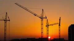 Timelapse sunset and silhouette crane working in construction site, 4k UHD 2160p Stock Footage