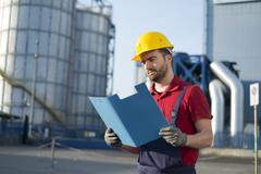 Laborer outside a factory working dressed with safety overalls equipment Stock Photos
