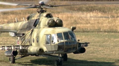 Wind shot Military helicopter landing on battlefield Stock Footage